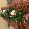 Greenery and flowers on a wicker coffin